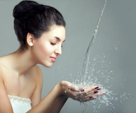 Woman and water splash. Water drops and bubbles in girls hands.